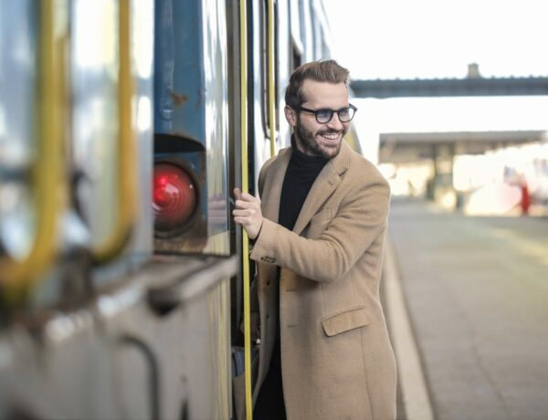 Adult male with a coat smiling getting on a train