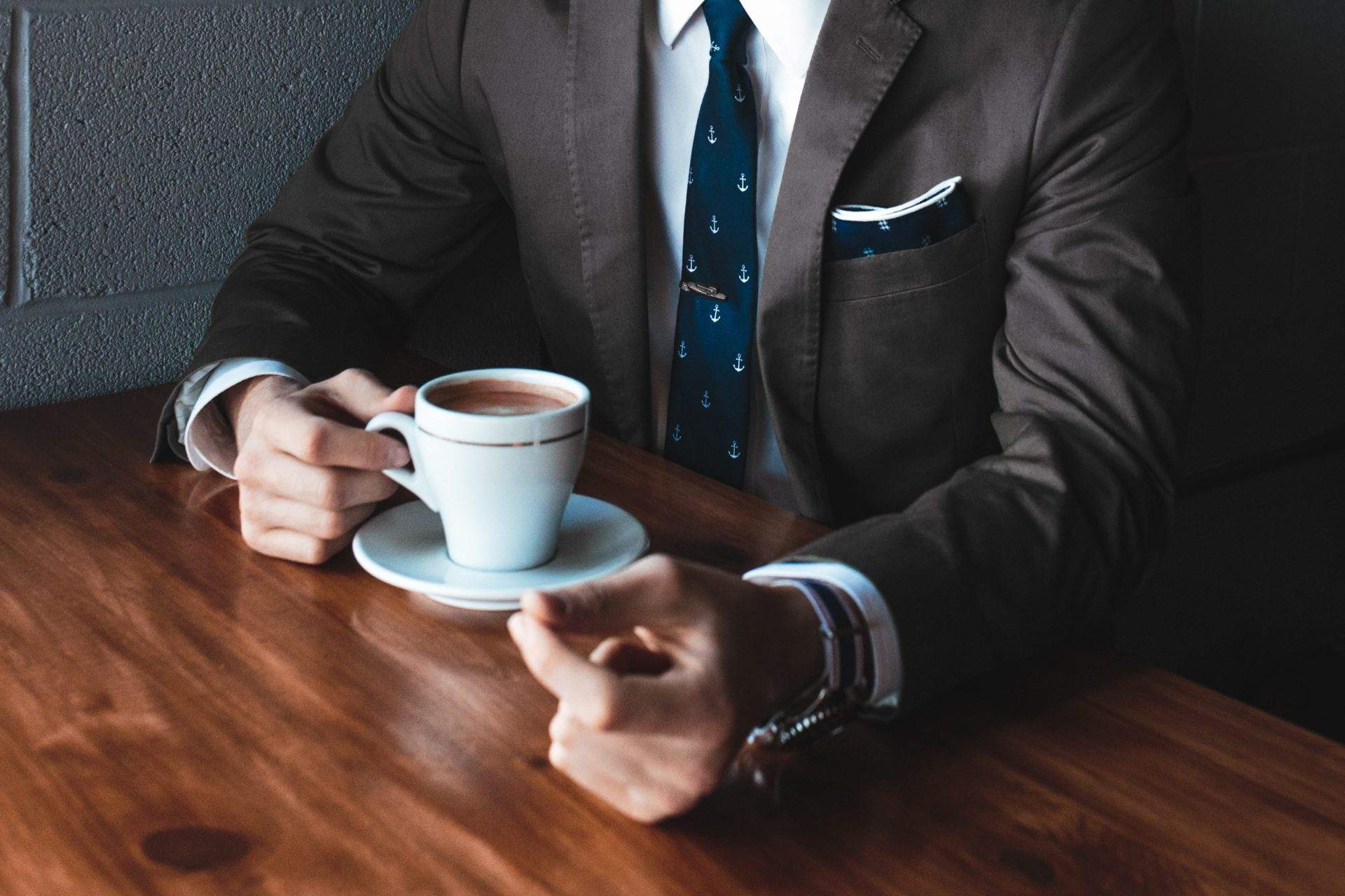 Man in suit holding a cup of coffee on a desk