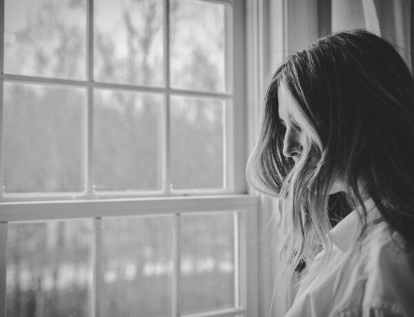 Grey photo women with hair over face near window looking down