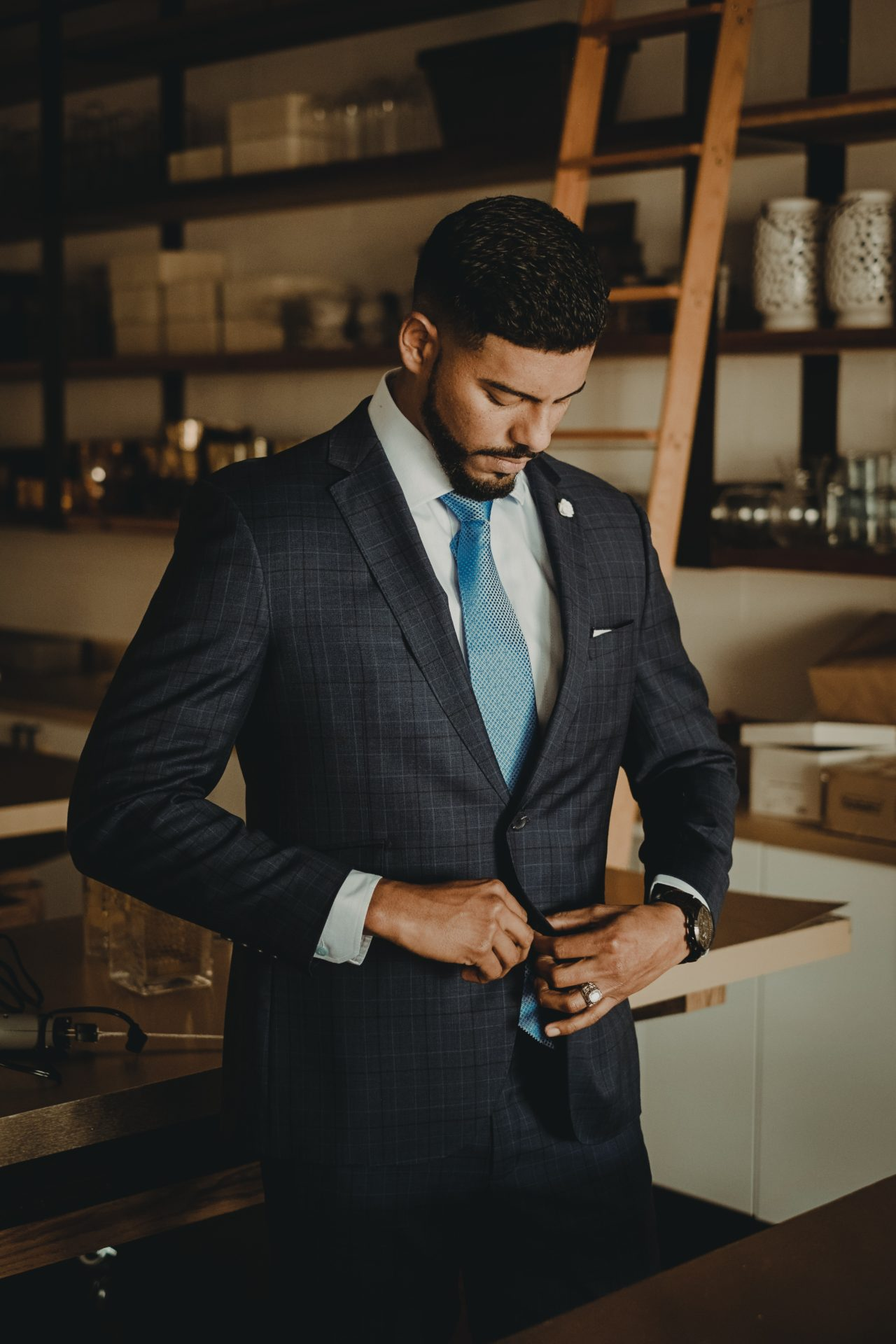 Man with beard standing up buttoning up suit with blue tie