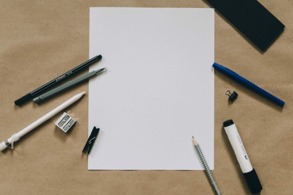 Blank piece of paper with pens and pencils around it