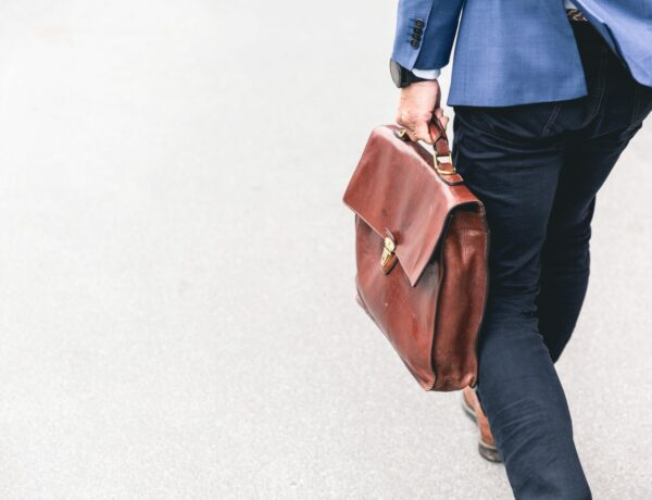 Man in blue suit with jeans holding brown briefcase walking away