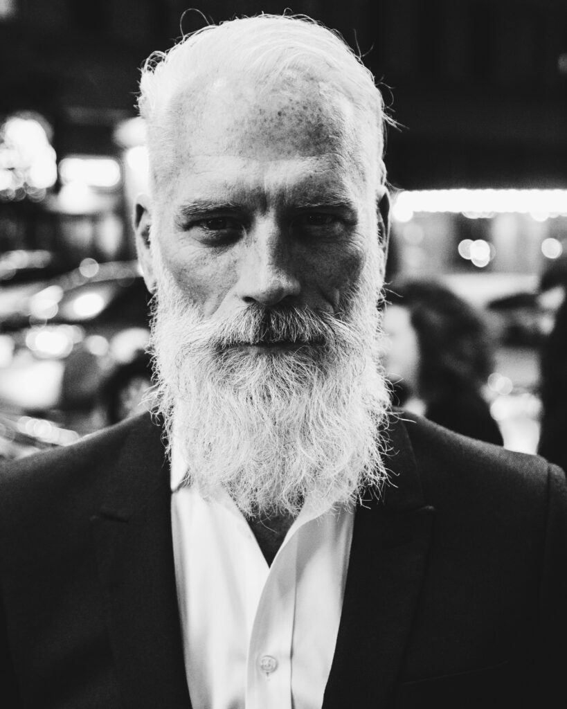 older man with a long white beard wearing a suit