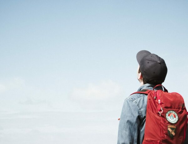 Man in cap with backpack staring at the blue sky