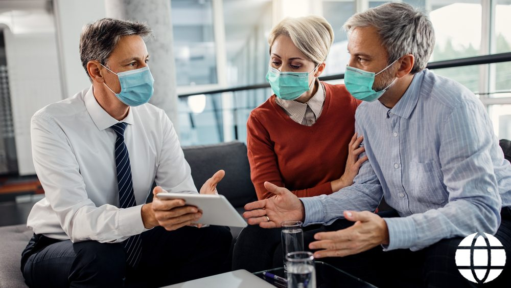 Independent Financial advisor with middle-aged clients wearing masks in office